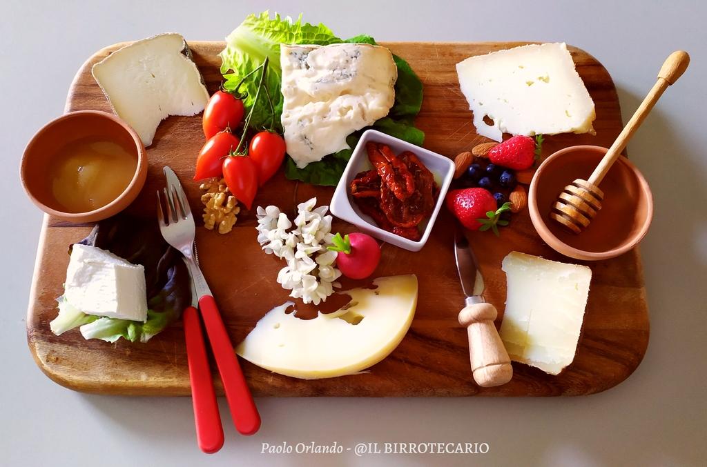Tagliere di formaggi con miele e pomodorini.